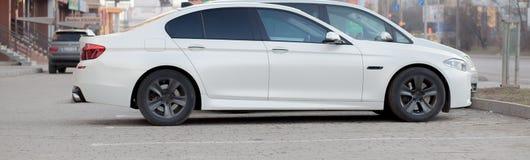 Zijaanzicht van witte auto die op bedekt parkeerterreingebied wordt geparkeerd op de vage achtergrond van de voorstadweg op helde royalty-vrije stock fotografie