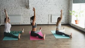 Zijaanzicht van yogastudenten die uitrekkende oefeningen doen die flexibiliteit ontwikkelen Drie vrouwen zitten op kleurrijke mat stock footage
