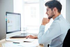 Zijaanzicht van zakenmanzitting die personal computer in bureau met behulp van stock afbeelding
