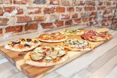 Zijaanzicht van zes verschillende pizza's op een houten raad stock foto