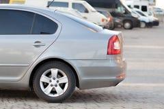 Zijaanzicht van zilveren die auto op bedekt parkeerterreingebied wordt geparkeerd op de vage achtergrond van de voorstadweg op he stock foto's
