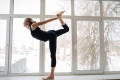 Zijaanzichtportret die van het aantrekkelijke jonge blondevrouw uitwerken in geschiktheidsclub of thuis, yoga doen die zich in ex stock foto