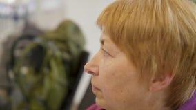 Zijaanzichtportret van oude vrouwenzitting bij luchthaven en wachten voor reis stock footage