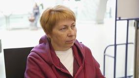 Zijaanzichtportret van oude vrouwenzitting bij luchthaven en wachten voor reis stock video