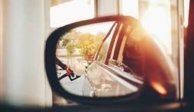 Zijaanzichtspiegel met de handen van de brandstof bijtankende dienst voor de auto royalty-vrije stock foto's
