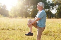 Zijdelings geschoten van gezonde bejaarde mannelijke rek heeft de benen, ernstige uitdrukking, draagt sportkleren en de schoenen, royalty-vrije stock foto