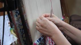 Zijdetapijt met geweven hand Twee vrouwen weven met de hand zijdetapijt stock footage