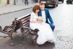 Zijfoto van de vrolijke jonggehuwden die op de bank zitten en het huwelijksboeket houden Royalty-vrije Stock Afbeelding