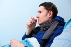 Zijfoto van ziek donkerbruin mannetje die neusnevel gebruiken terwijl het liggen in bed stock foto's