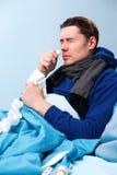 Zijfoto van ziek donkerbruin mannetje die neusnevel gebruiken terwijl het liggen in bed stock fotografie
