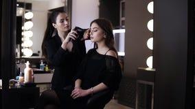 Zijlengte van jong mooi meisje in zwarte tijdens het make-upproces met luchtpenseel Mooie donkerbruine vrouwelijke kunstenaar stock footage