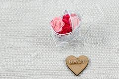 Zijn babykaart - een meisjesthema Gouden brieven Word baby op hout Kinderwagenhoogtepunt van bloemen op witte textielachtergrond  Royalty-vrije Stock Foto