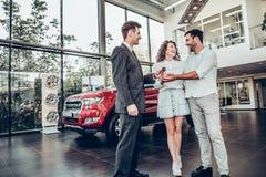 Zijn goede keus! De autoverkoper geeft de sleutel van de nieuwe auto aan de jonge aantrekkelijke eigenaars royalty-vrije stock afbeelding