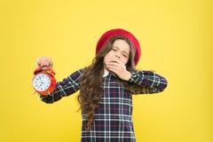 Zijn tijd om naar slaap te gaan Slaperig meisje in avondtijd op gele achtergrond De holdingsalarm van het geeuw klein kind stock foto's