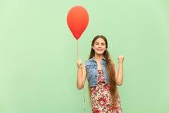 Zijn winn! De mooie blondetiener met rode ballons op een groene achtergrond Stock Foto's