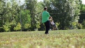 Zijn zoon houden door de hand en vader die rond omcirkelen stock videobeelden