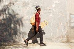 Zijportret van de jonge Afrikaanse Amerikaanse mens die buiten met skateboard lopen stock afbeeldingen