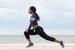Zijportret van gezonde jonge Afrikaanse Amerikaanse vrouw het uitrekken zich spieren bij het strand stock afbeelding