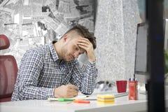 Zijprofielschot die van gefrustreerde jonge donkerbruine ondernemer, bij zijn laptop in bureau en klemmen de documenten schreeuwe stock foto's