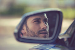 Zijspiegelbezinning van een jonge mens die zijn nieuwe auto drijven Royalty-vrije Stock Foto's