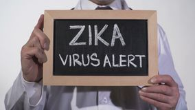 Zika virus alert written on blackboard in therapist hands, infectious disease. Stock footage stock video footage