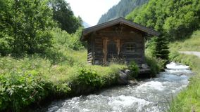 Zillertal Alps stream water though forest and mountains. Hohe Tauern nation park. Small typical wooden house stock footage