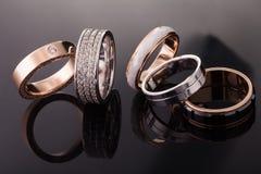 Zilver, goud, platinaringen van verschillende stijlen op de donkere achtergrond van bezinningen Royalty-vrije Stock Foto