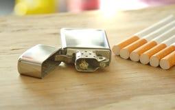Zilveren aansteker en sigaret aan boord stock foto