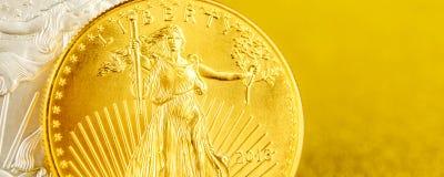 Zilveren adelaar en gouden Amerikaanse adelaar ??n onsmuntstukken op gouden achtergrond stock afbeelding