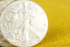 Zilveren adelaar en gouden Amerikaanse adelaar ??n onsmuntstukken op gouden achtergrond stock foto's