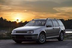 Zilveren auto bij zonsondergang Stock Foto's