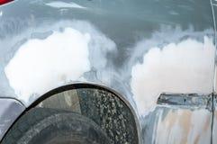 Zilveren auto met beschadigde verf en gedeukt metaallichaam van neerstortingsongeval met onvolledige carrosserie over gebarsten e stock foto