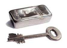 Zilveren baar en sleutel tot de brandkast Geïsoleerdj op witte achtergrond stock afbeelding
