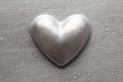 Zilveren beeldje in de vorm van harten op een metaalplaat Royalty-vrije Stock Foto