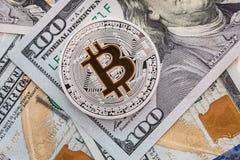 Zilveren bitcoin ligt op 100 dollarsrekeningen Bitcoin op dollarsachtergrond Stock Foto's