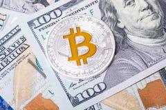 Zilveren bitcoin ligt op 100 dollarsrekeningen Bitcoin op dollarsachtergrond Het concept van de mijnbouw Royalty-vrije Stock Foto