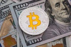 Zilveren bitcoin ligt op 100 dollarsrekeningen Bitcoin op dollarsachtergrond Het concept van de mijnbouw Stock Foto