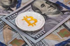 Zilveren bitcoin ligt op 100 dollarsrekeningen Bitcoin op dollarsachtergrond Het concept van de mijnbouw Royalty-vrije Stock Fotografie
