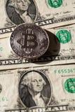 Zilveren bitcoinmuntstuk die op de dollars van Verenigde Staten, cryptocurrencyconcept liggen Stock Afbeeldingen