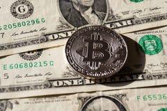 Zilveren bitcoinmuntstuk die op de dollars van Verenigde Staten, cryptocurrencyconcept liggen Royalty-vrije Stock Fotografie