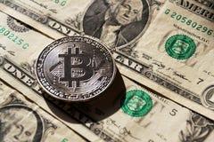 Zilveren bitcoinmuntstuk die op de dollars van Verenigde Staten, cryptocurrencyconcept liggen Royalty-vrije Stock Foto's