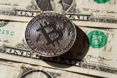 Zilveren bitcoinmuntstuk die op de dollars van Verenigde Staten, cryptocurrencyconcept liggen Stock Foto
