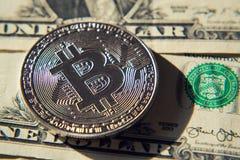 Zilveren bitcoinmuntstuk die op de dollars van Verenigde Staten, cryptocurrencyconcept liggen Royalty-vrije Stock Afbeelding