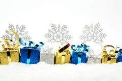 Zilveren, blauwe, gouden Kerstmisgiften met sneeuwvlokken op sneeuw Stock Afbeeldingen