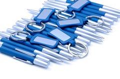 Zilveren-blauwe metaalpennen en keychains geïsoleerd op wit royalty-vrije stock fotografie