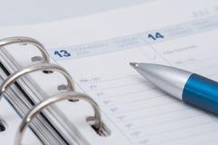 Zilveren blauwe pen op open bedrijfsagenda Royalty-vrije Stock Afbeeldingen