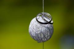 Zilveren bruiloftringen op geweven van dradenbal Stock Foto