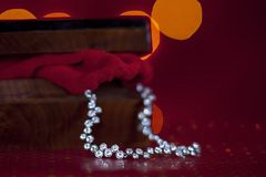 Zilveren diamantketting in een mooie houten kist met rode achtergrond stock foto's