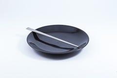Zilveren eetstokjes op zwarte ceramische plaat (op witte bac Royalty-vrije Stock Afbeeldingen