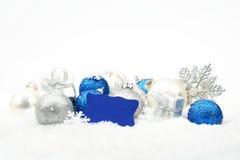 Zilveren en blauwe Kerstmisdecoratie op sneeuw met wensenkaart Stock Afbeeldingen